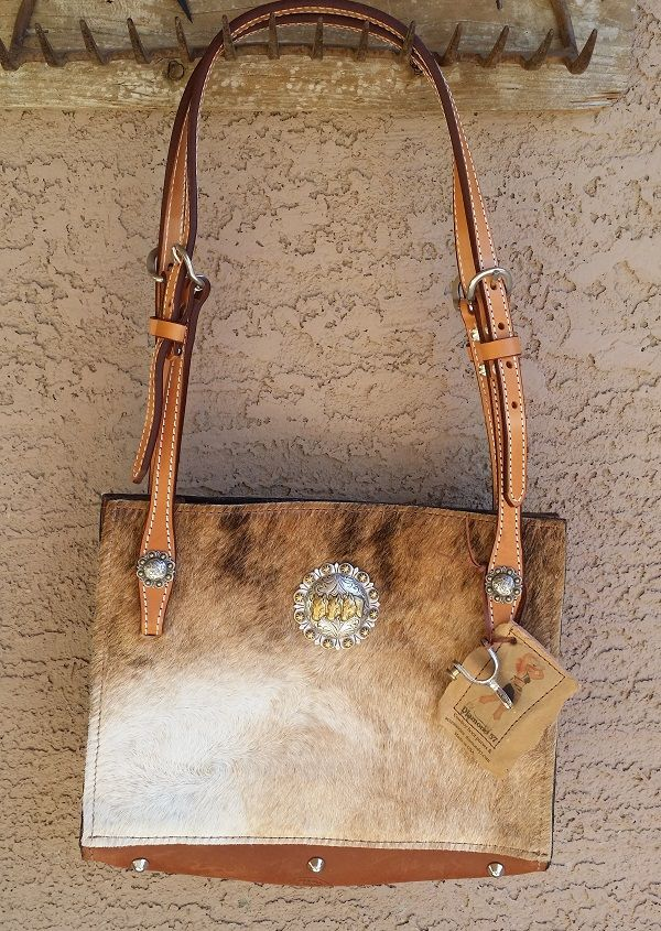 Blonde hair on cowhide bag with horse tack handles and concho