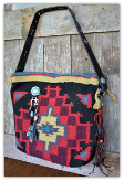 502a Red and black saddle blanket bag with tassels, trinkets and leather handle